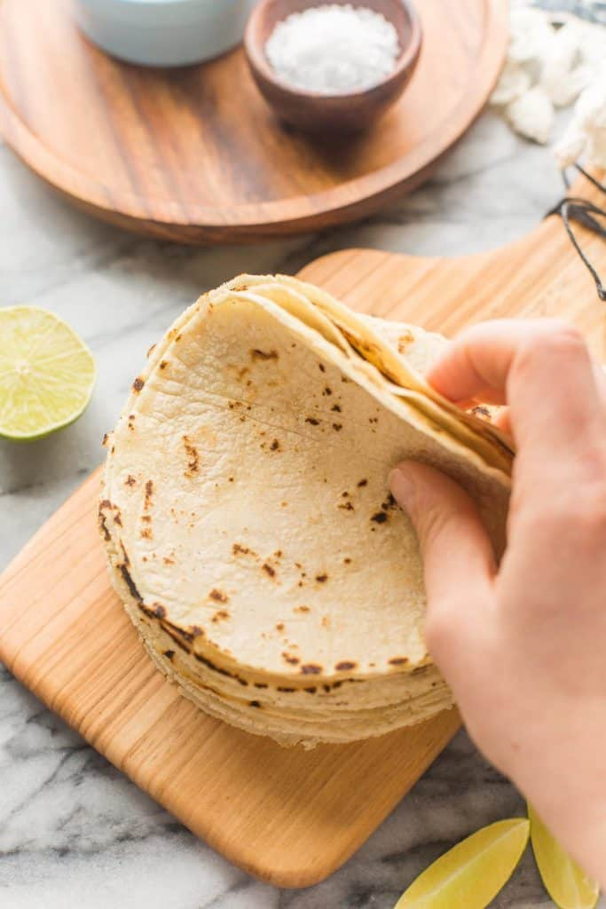 hand flipping back a stack of corn tortillas