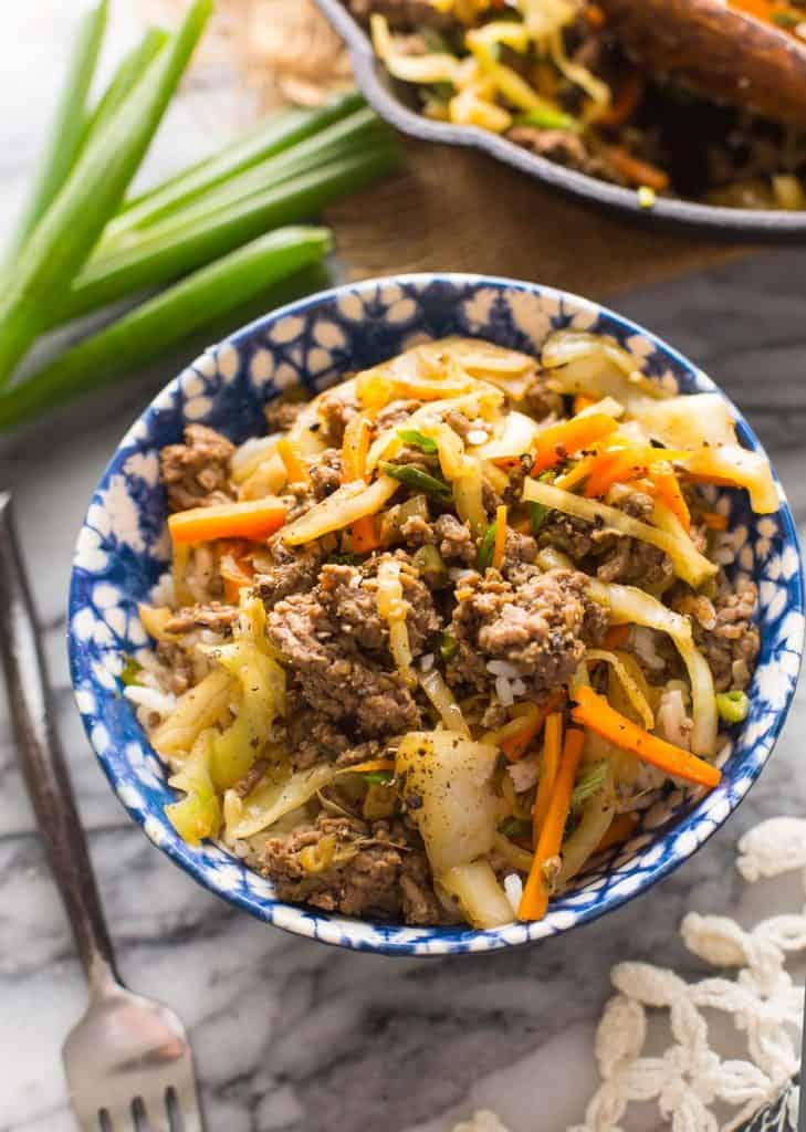 Beef and Cabbage Stir Fry in a blue and white bowl over rice