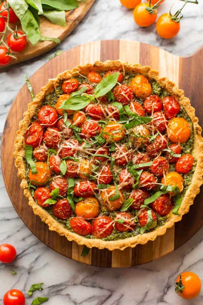 Almond Flour Tomato Tart topped with basil on a cutting board