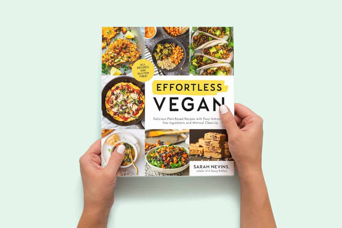 two hands holding a copy of the Effortless Vegan cookbook