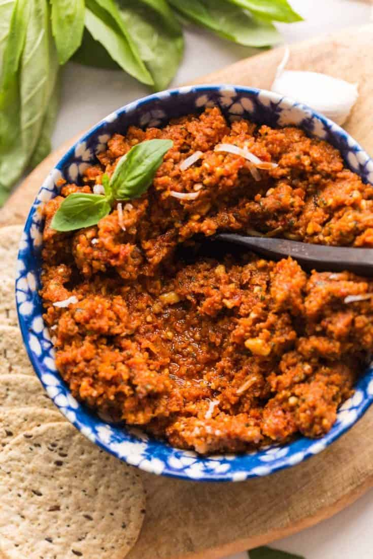 sun dried tomato pesto in a bowl topped with basil