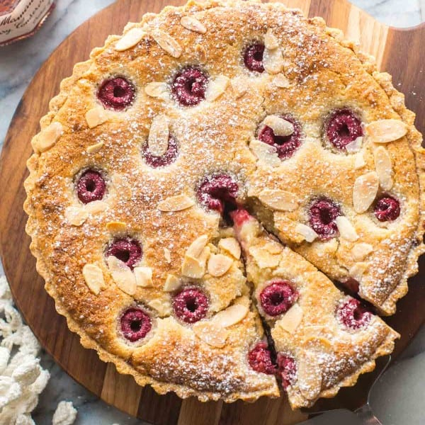 vegan bakewell tart on a wooden serving board with a slice cut out