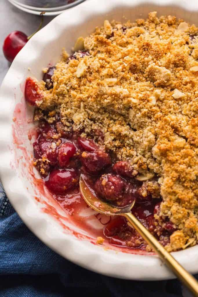 up close picture Grain Free Cherry Crumble in a a pie dish with the filling exposed