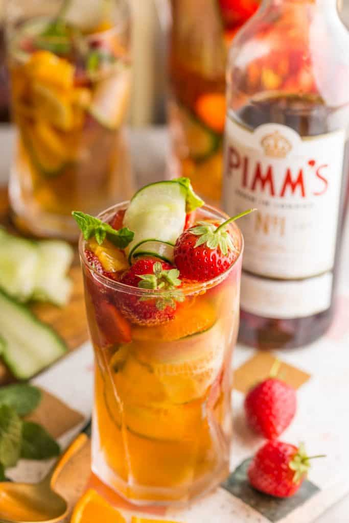 pimm's cup full of sliced cucumber, strawberries and orange slices