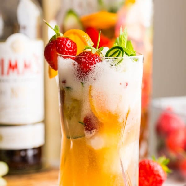pimm's cup float in a tall glass topped with fruit