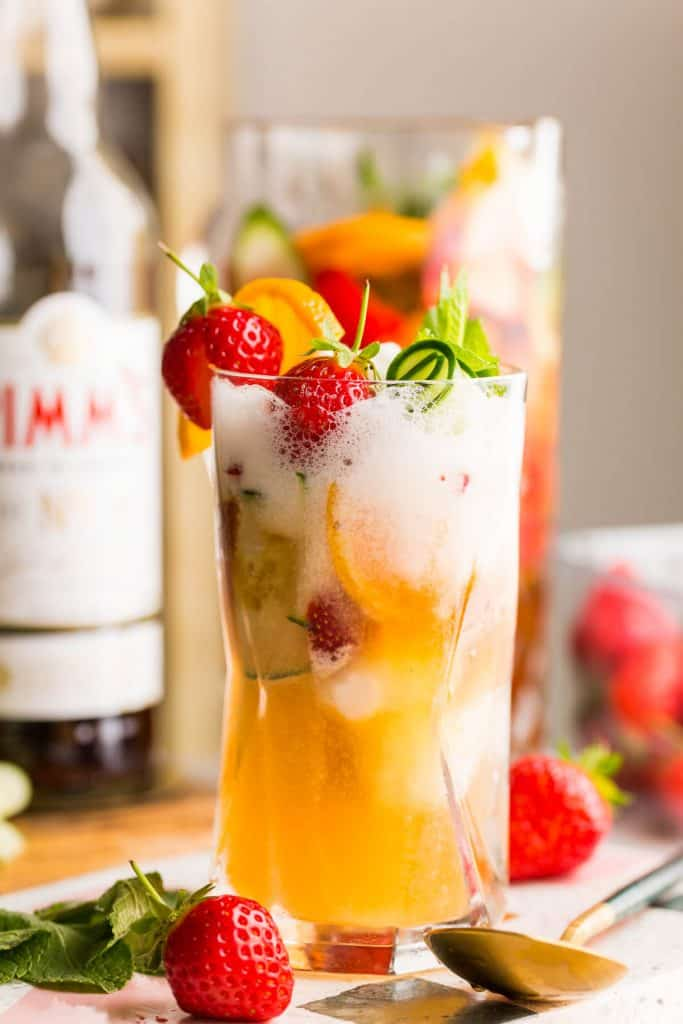 a pimm's cup float topped with fresh strawberries and cucumber