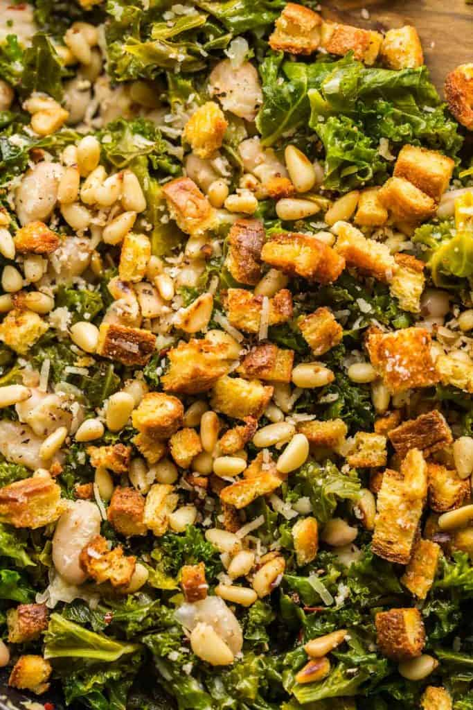 up close picture of cannelini and kale stir fry in a skillet topped with toasted bread and pine nuts