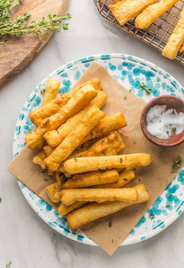 panisses (chickpea fries) arranged on a plate with a little bowl of salt