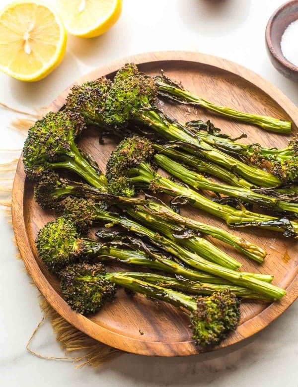 roasted tenderstem broccoli on a plate with lemons on the side