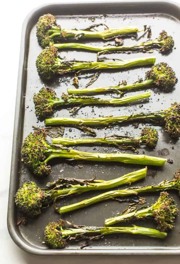 roasted tenderstem broccoli spread out on a baking sheet