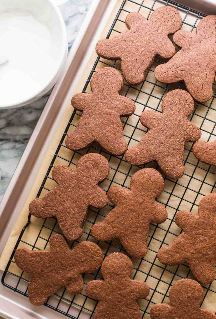 chocolate sugar cookies in the shape of gingerbread men cooling on a wire rack