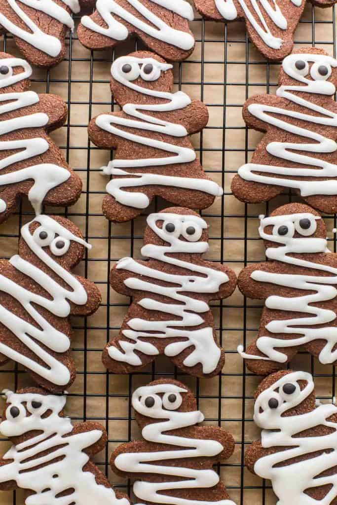 chocolate sugar cookies decorated like mummies on a wire rack