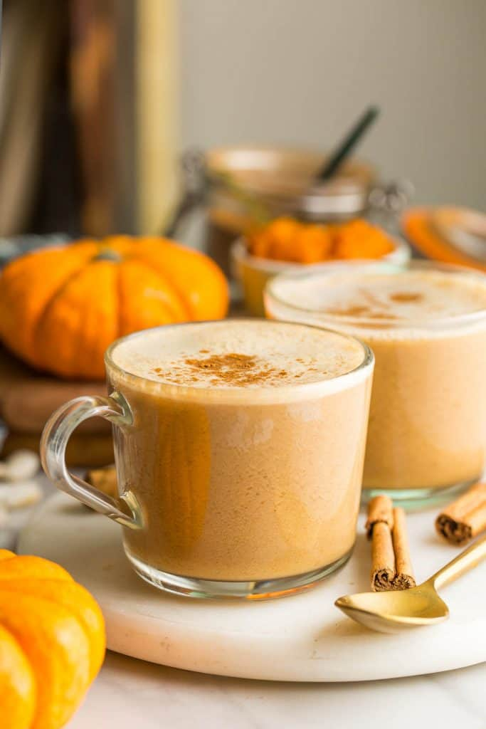 a couple of Dairy Free Pumpkin Spice Lattes topped with cinnamon with little pumpkins and cinnamon sticks