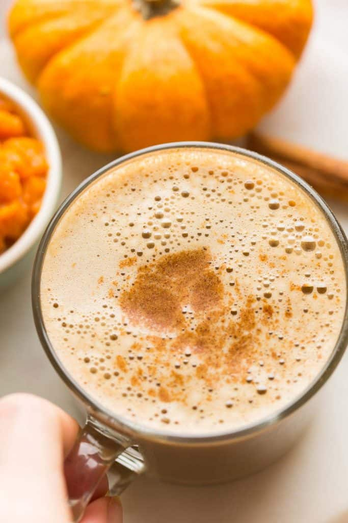 hand pick up a mug of Dairy Free Pumpkin Spice Latte