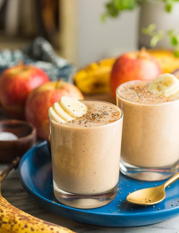 two apple banana smoothies on a plate with banana slices on top