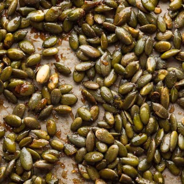 cinnamon spiced roasted pepitas on a baking sheet